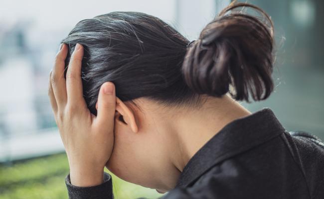 頭痛で頭をかかえる女性